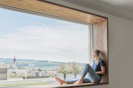 Frau sitzt auf der Fensterbank und schaut aus dem Fenster