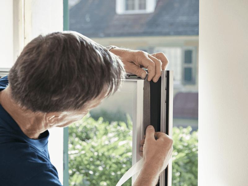 Monteur dichtet die Fenster vom Renovationsfenster ab