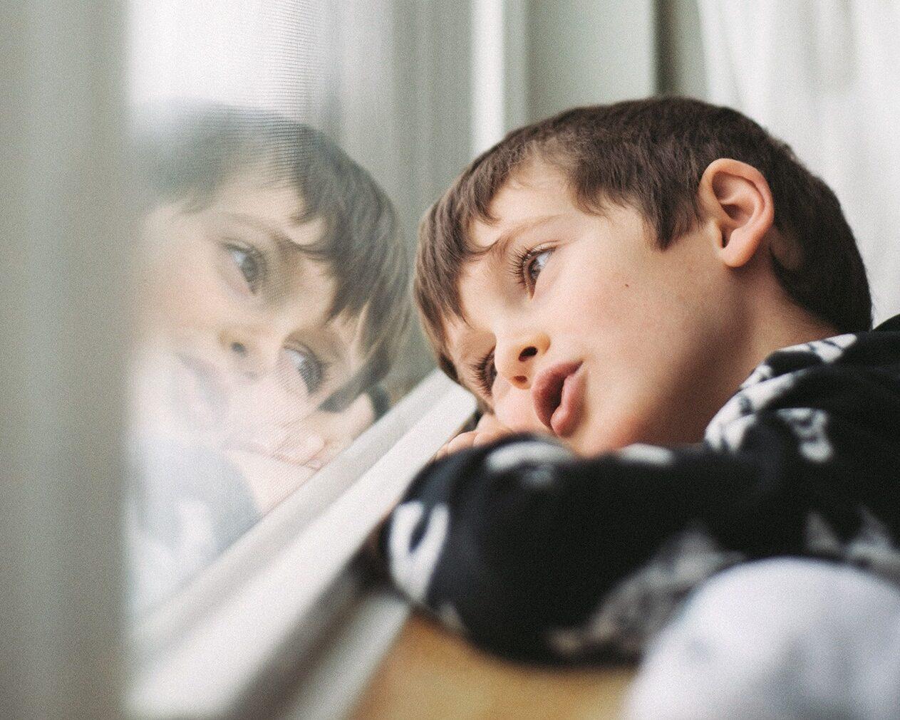 Petit garçon regardant rêveusement par la fenêtre