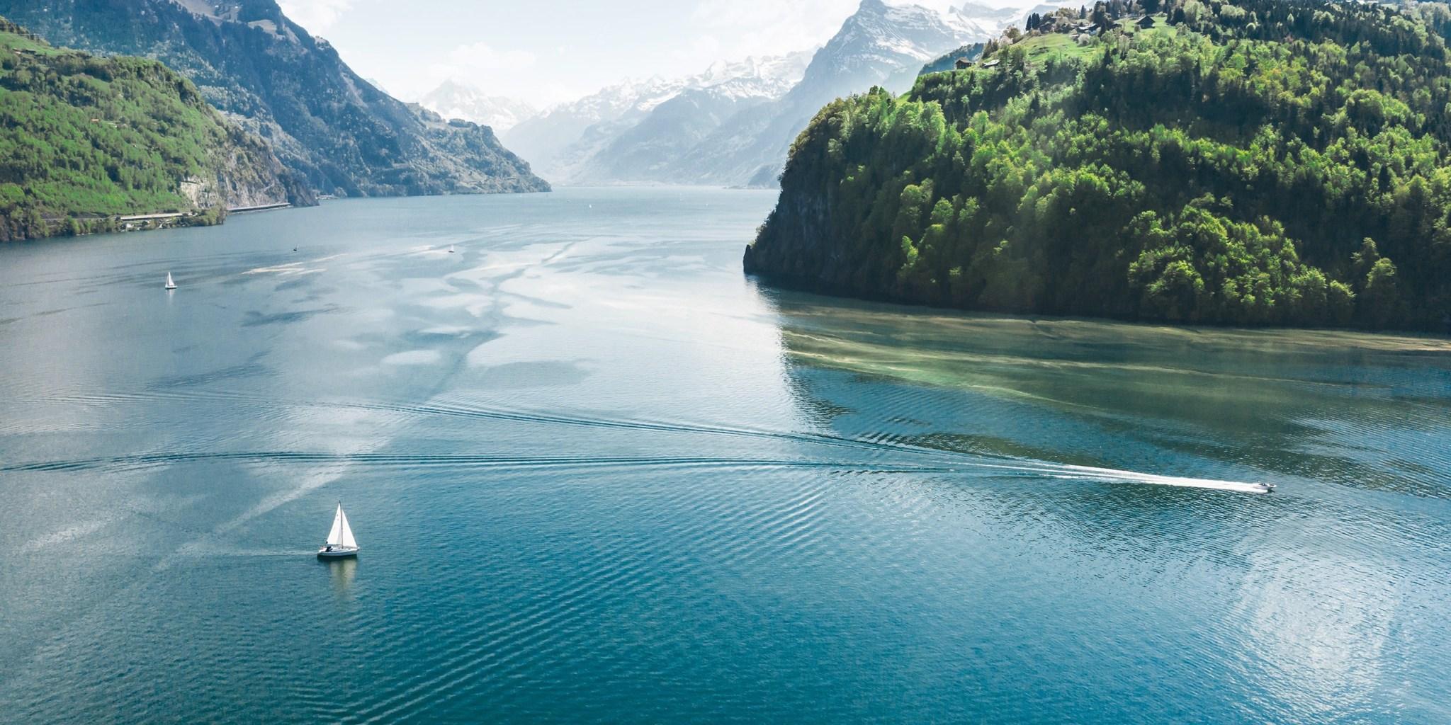 Landschaft mit Segelboot, See und Wald