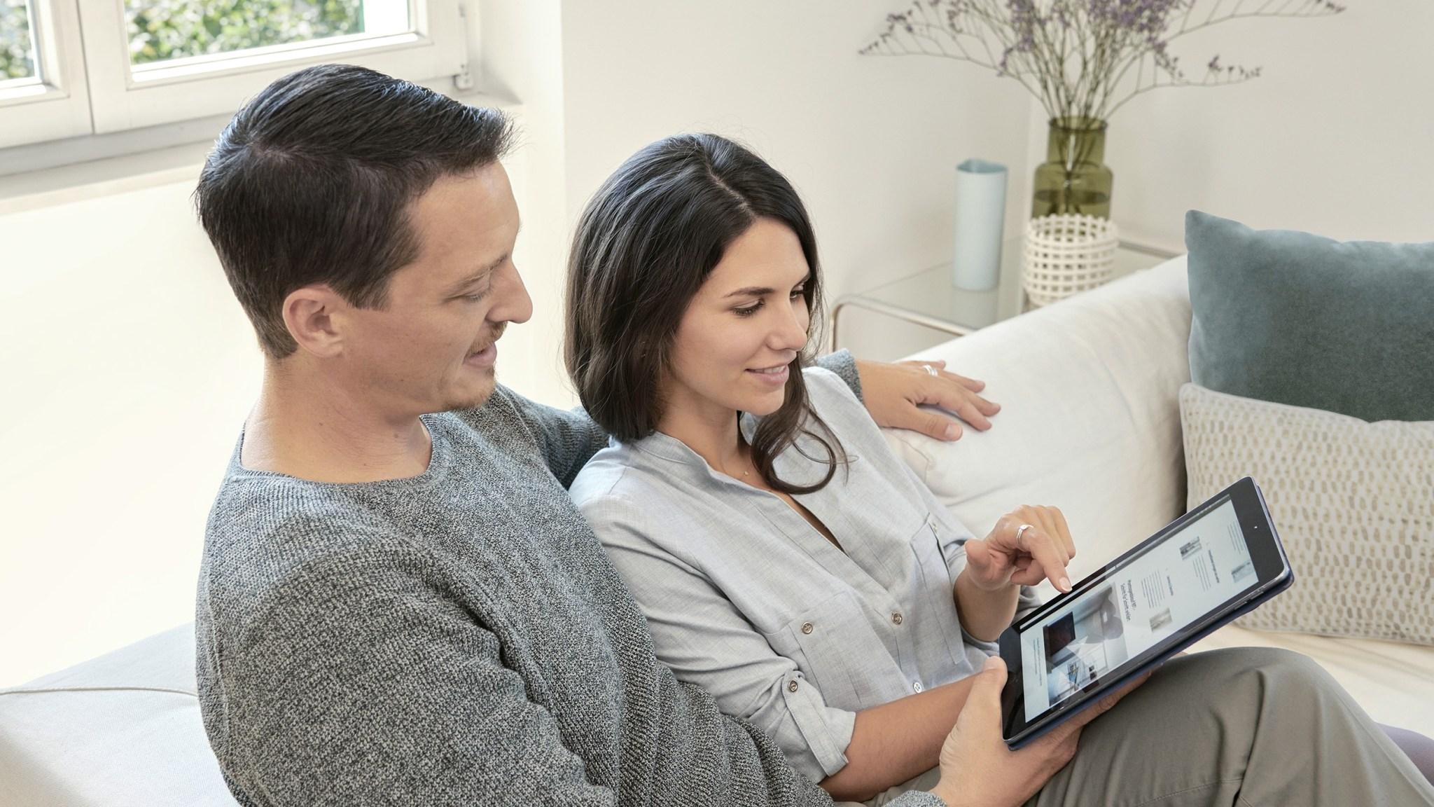 Jeune couple assis ensemble sur un canapé regardant le site web 4B sur une tablette.