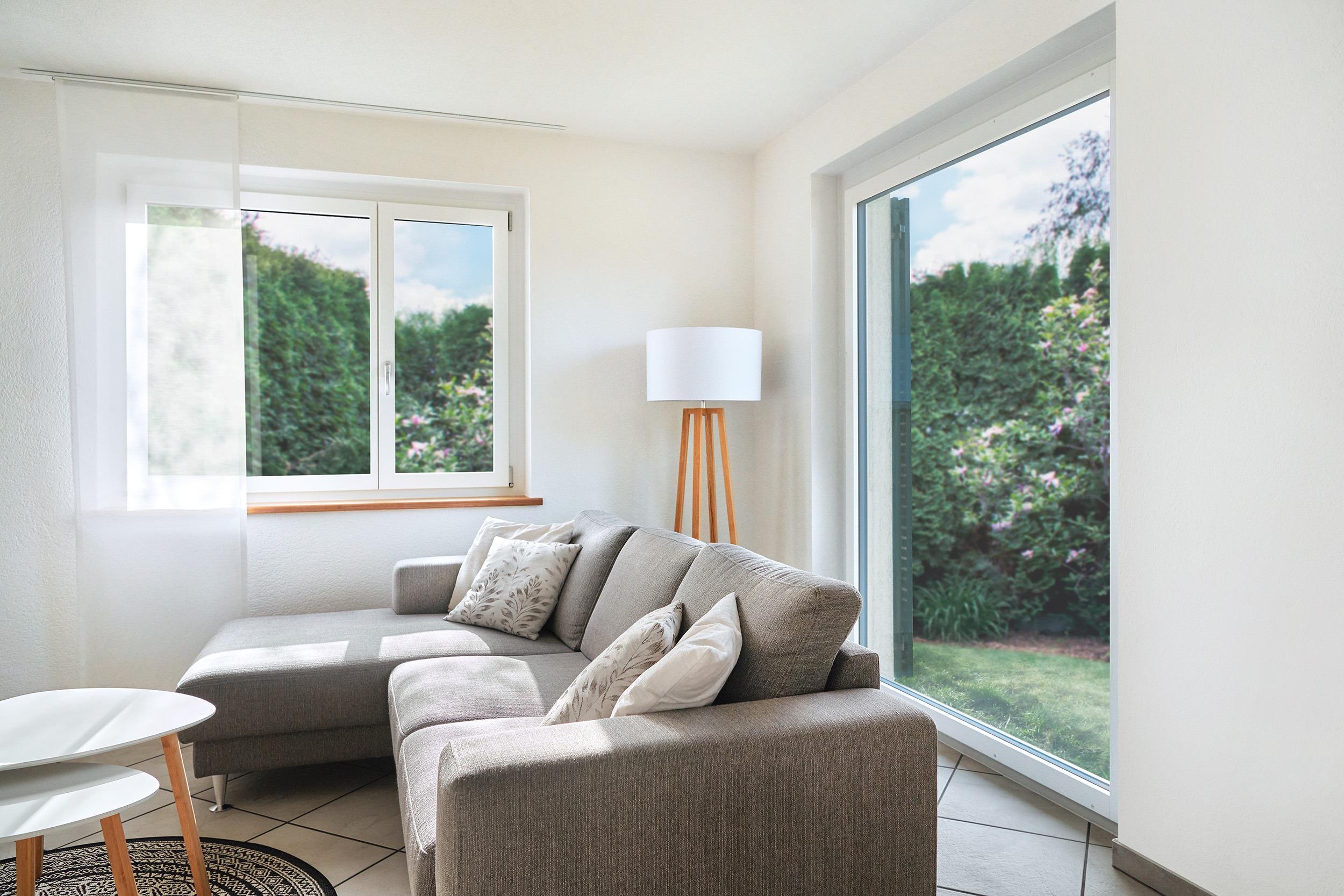 Wohnzimmer mit grauem Sofa, Kaffeetisch und grossen Fenstern.