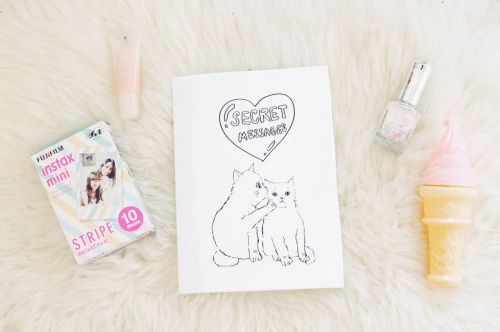 photo of an instant camera, lip gloss, a zine marked 'Secret Messages' featuring two cats conversing, nail polish, and an object shaped like a strawberry ice cream cone, on a white shag carpet