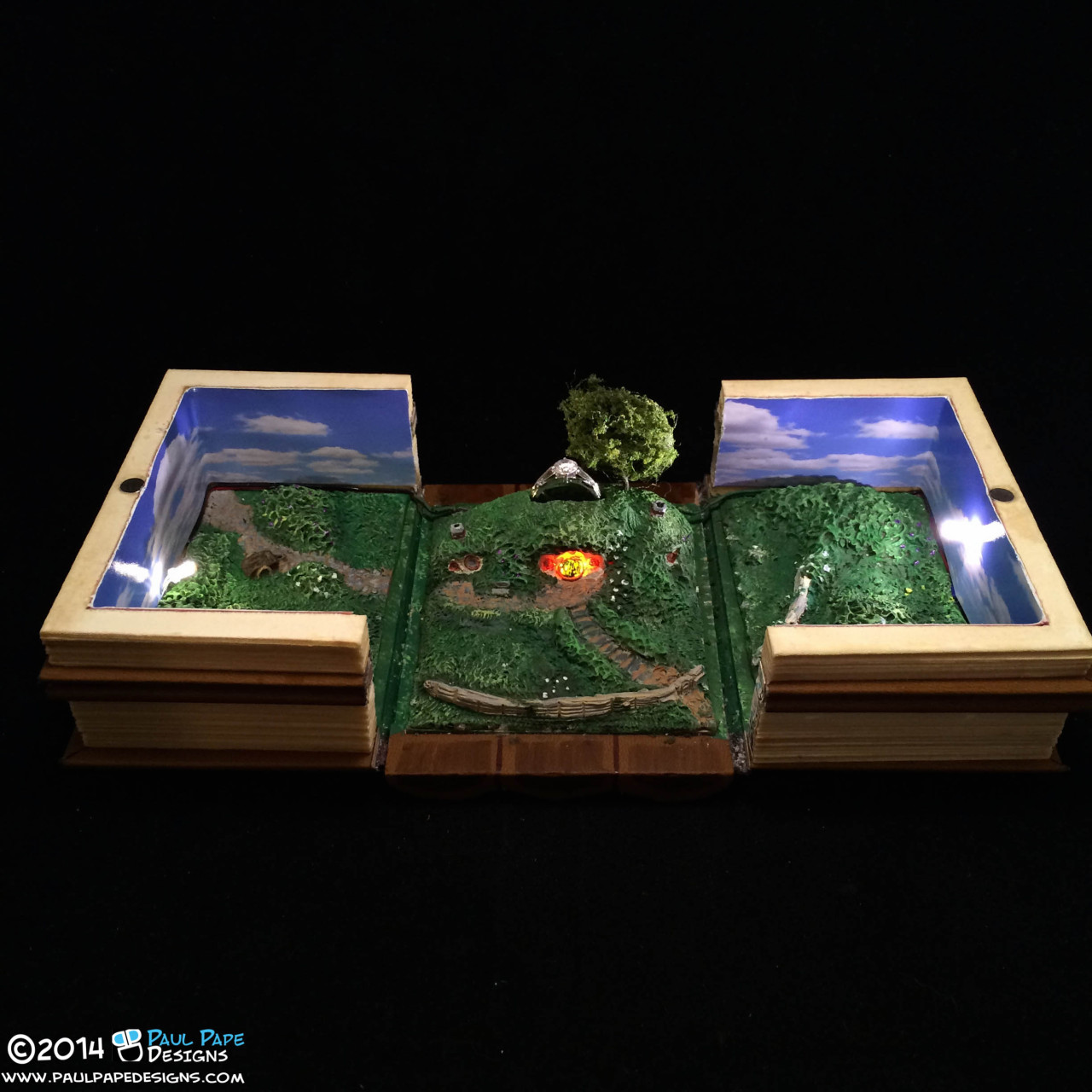 Lord of the Rings Bad End Custom Engagement Ring Box by Paul Pape Designs. This is a ring box based on the J.R.R. Tolkien series the Lord of the Rings. It is a series of books, and then when you open the books you're presented with Bag End in the Shire, and the ring is situated above Frodo's house.