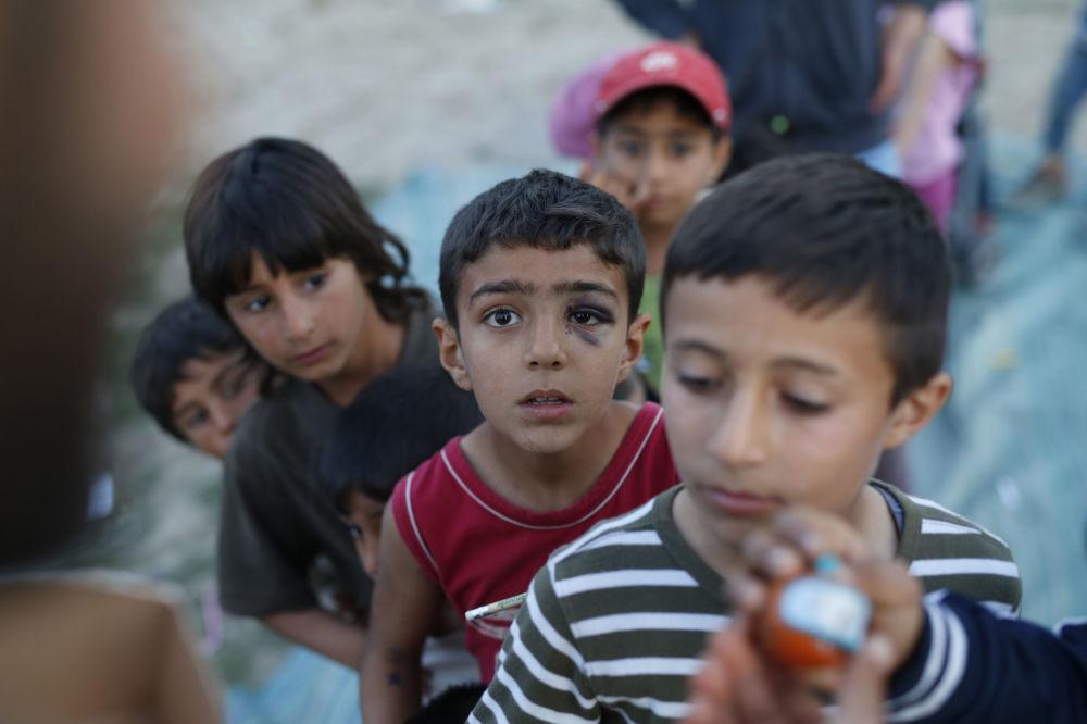 Bambini migranti stanno in fila per ricevere un giocattolo nel campo profughi di Idomeni.  Amel Enric