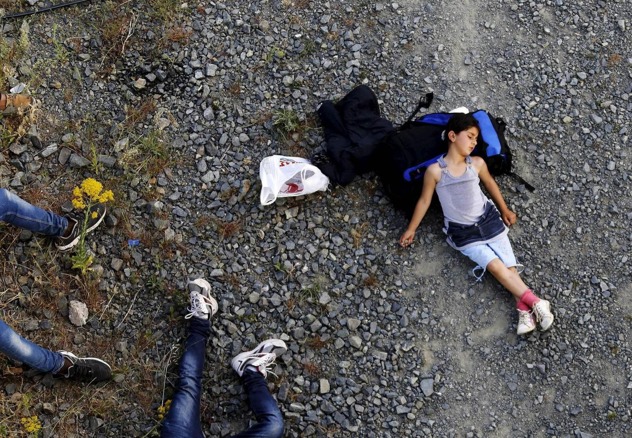 Seven year-old Ariana, a Kurdish-Syrian immigrant, rests before crossing into Macedonia along with another 45 Syrian immigrants near the border Greek village of Idomeni in Kilkis prefecture. REUTERS/Yannis Behrakis