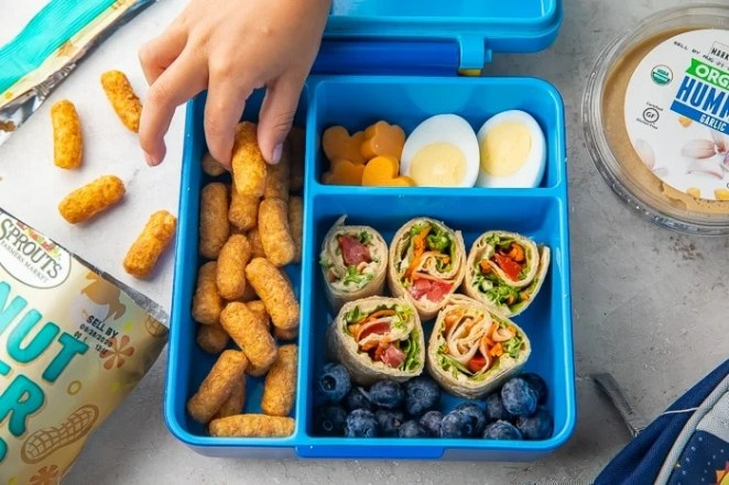 Child's hand reaching into easy vegetarian bento box for kids