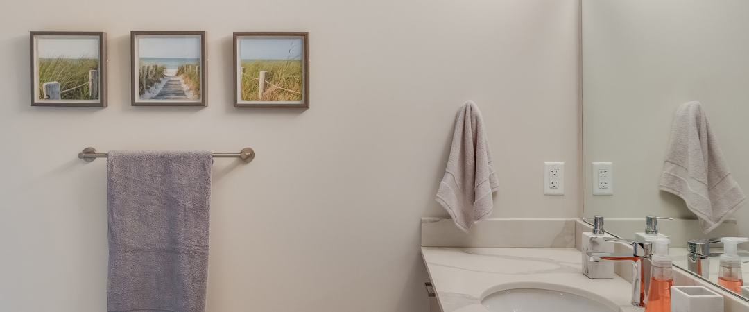 Sink next to towel holders mounted to the wall - one holds a hand towel and the other a full sized towel