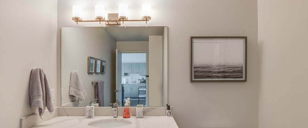 Sink with large mirror above it and rose gold vanity light featuring four lights