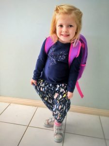 Young girl dressed for first day of school at Kinder.