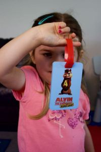 Girl holds a Chipmunk luggage tag
