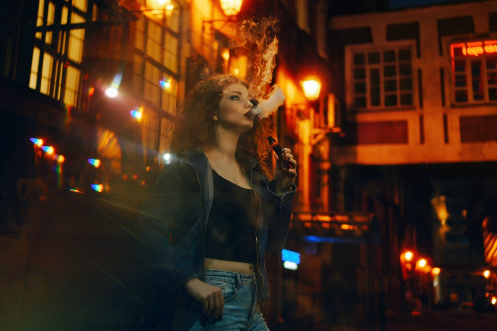 attractive red-haired girl vaping eCig