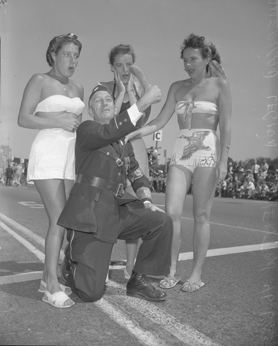 Man wearing gag thumb with three bathing beauties, Long Beach, CA  --1949.  Someone please explain...