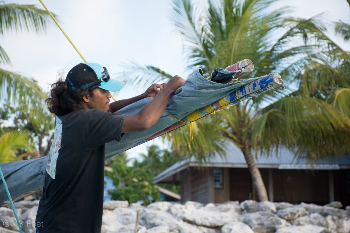 marshallese man putting away sailing canoe, ailuk atoll, marshall islands