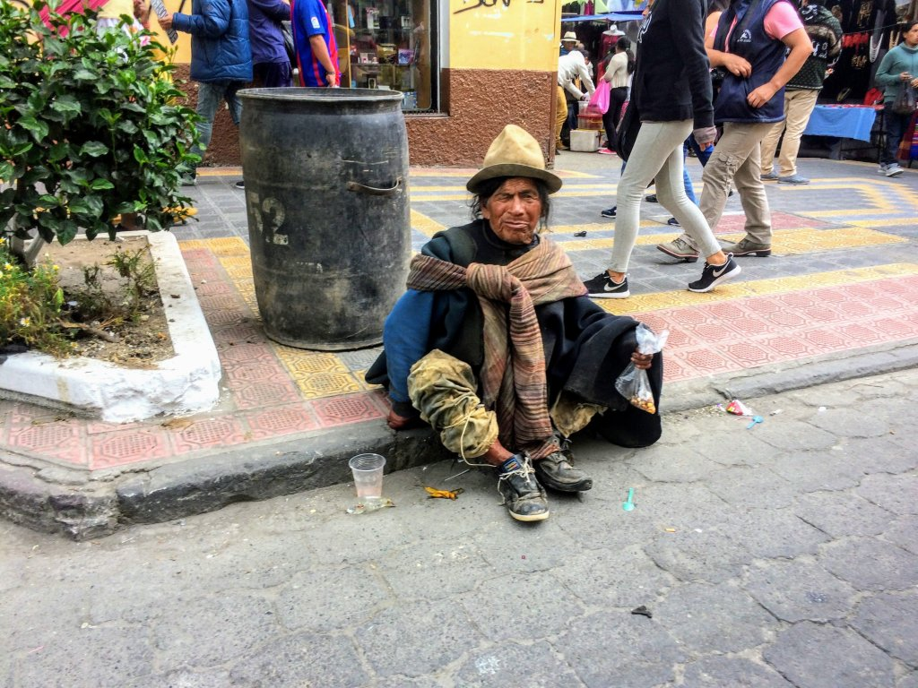 A homeless man begging in Otovalo Ecuador