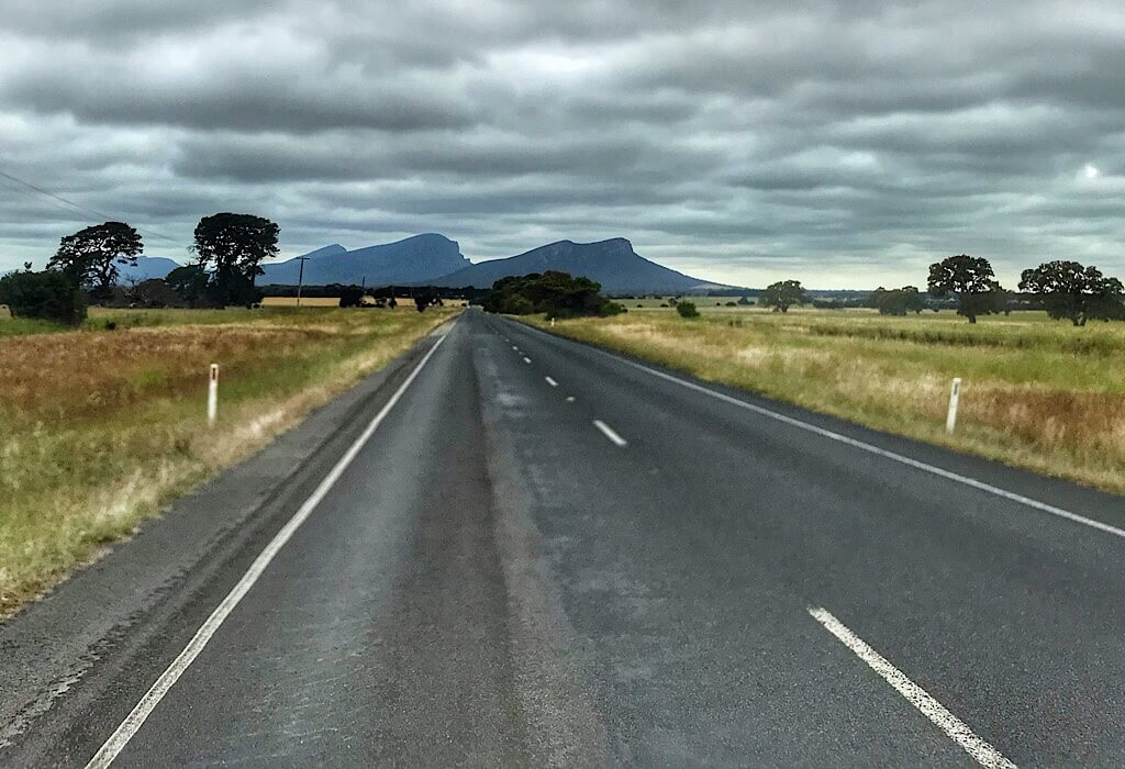 A road surrounded by golden plains with the Grampians in the distance