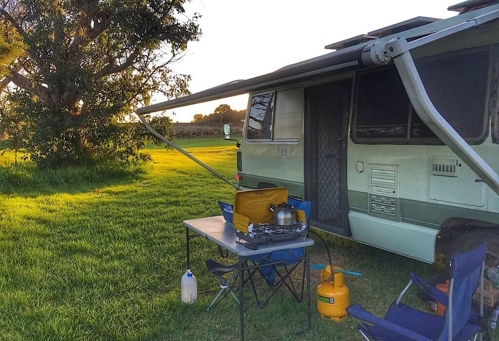 Lil' Beaut the bus with the awning extended and camp table set up outside