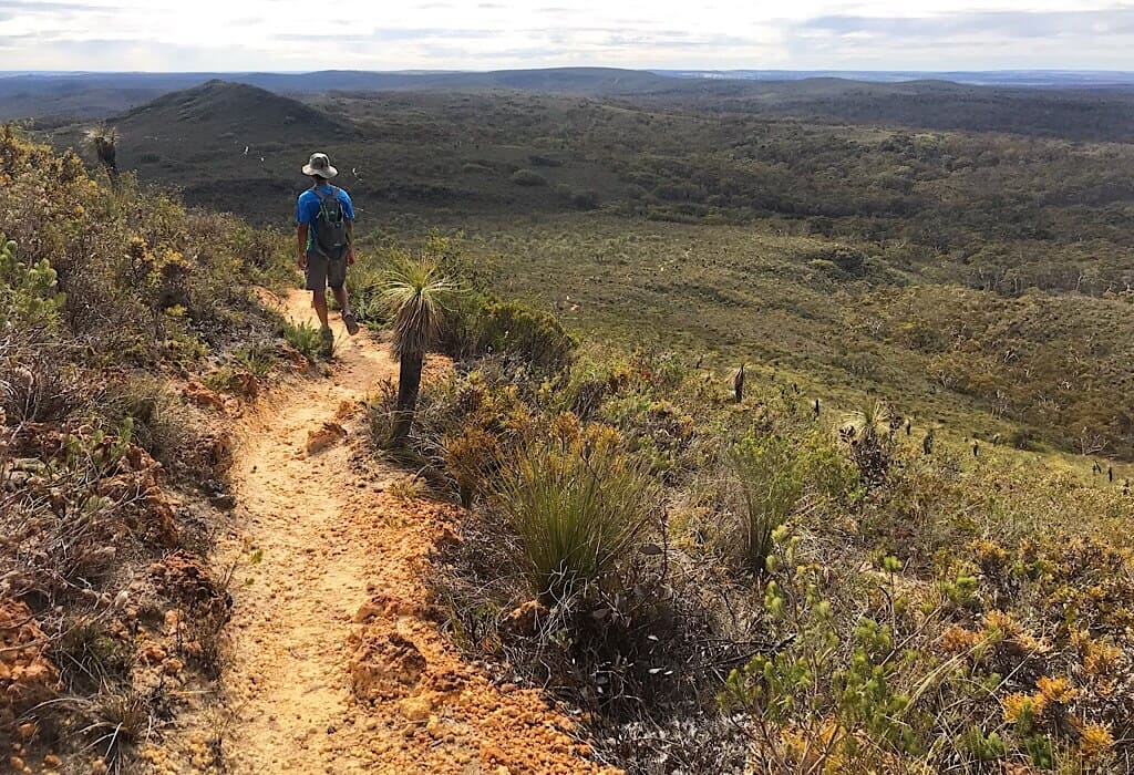 Trin on a path in Lesueur National Park, the valley stretches below and another small peak is in the distance.