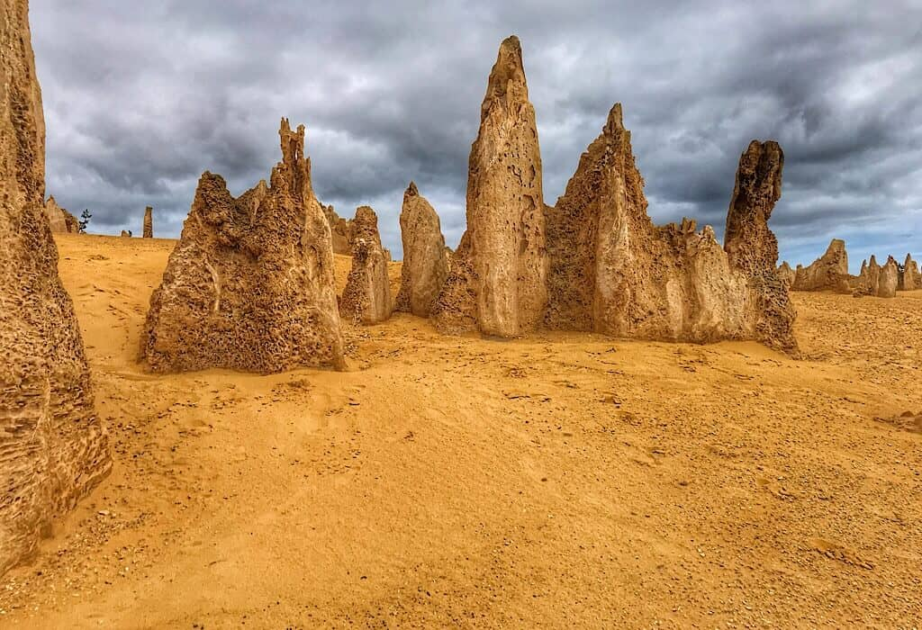 A group of pinnacles standing at the top of a sand dune