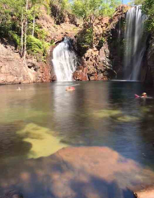 Two waterfalls descend into a deep plunge pool with crystal clear waters.