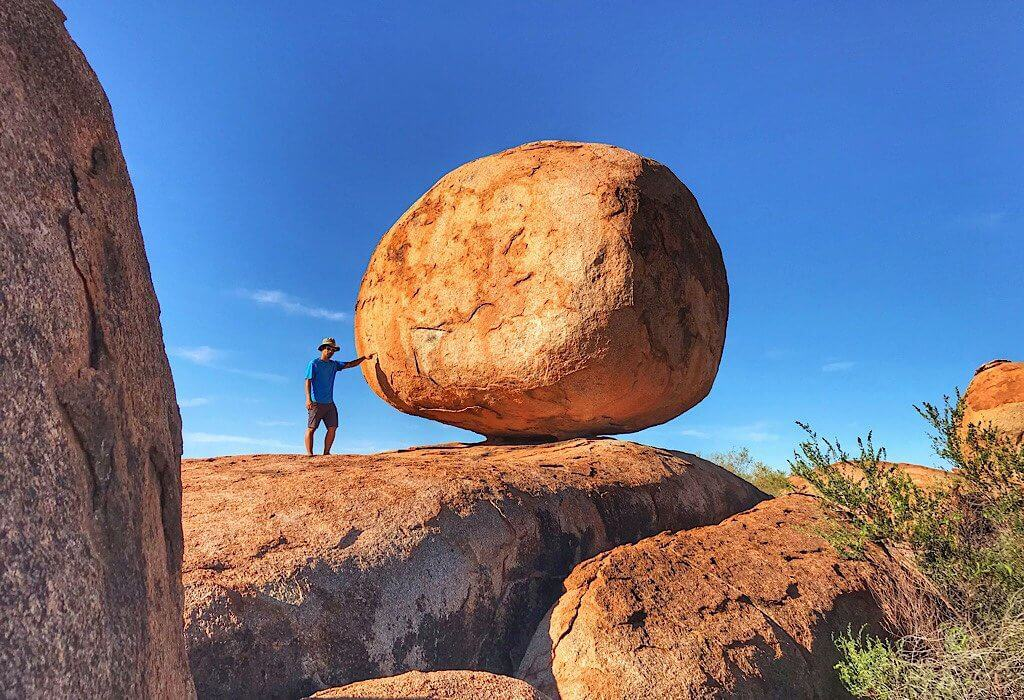Trin beside one of the large granite boulders of Devils Marbles in the red center of the Northern Territory