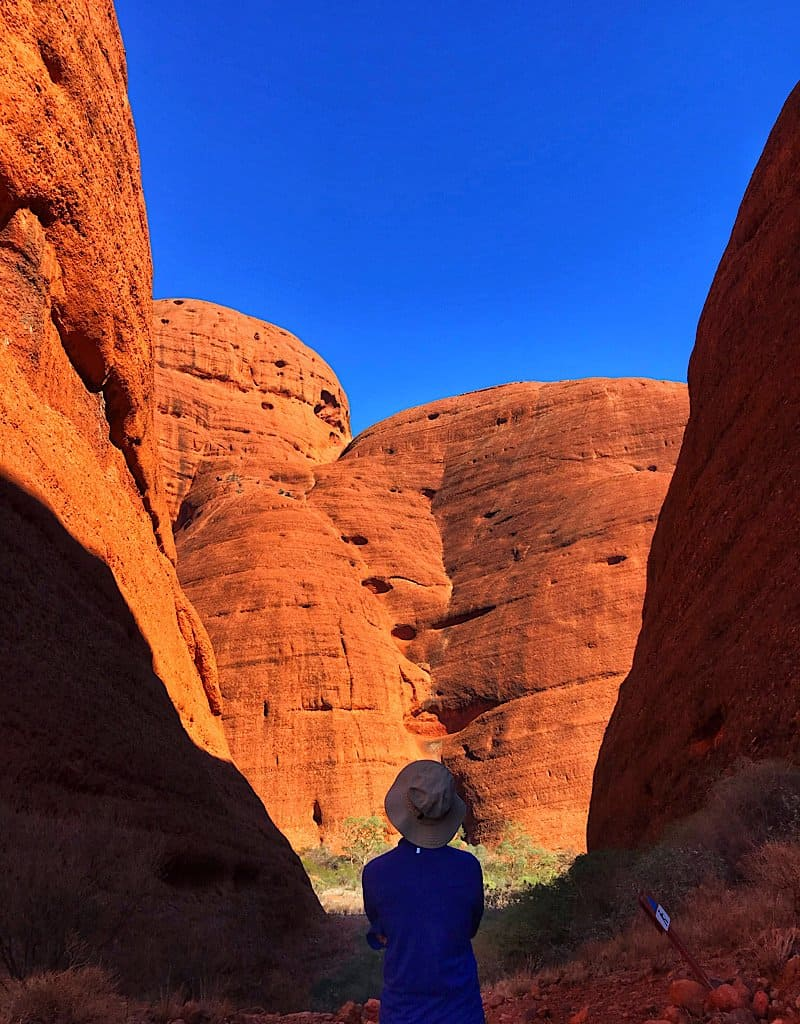 Trin between two of the boulders at Kata Tjuta (The Olgas). The sun reflecting off the red surface.
