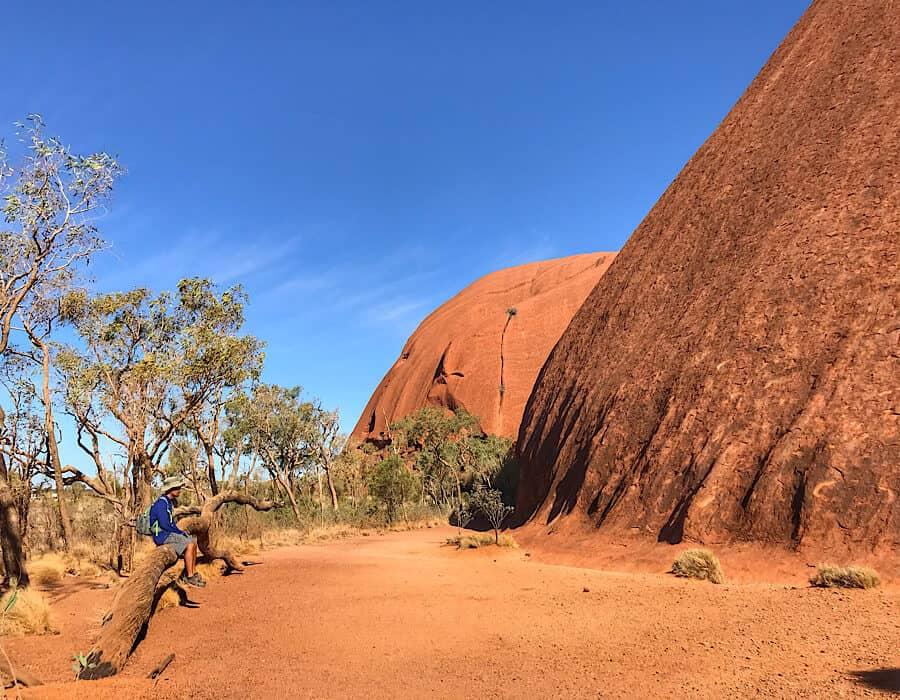 Where the base of Uluru meets the sandy desert