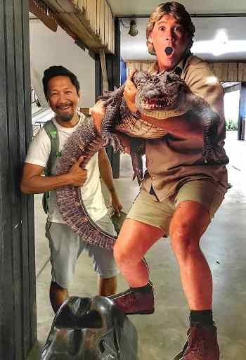Trin holding a crocodile tail behind Steve Irwin (Irwin and crock are a statue)