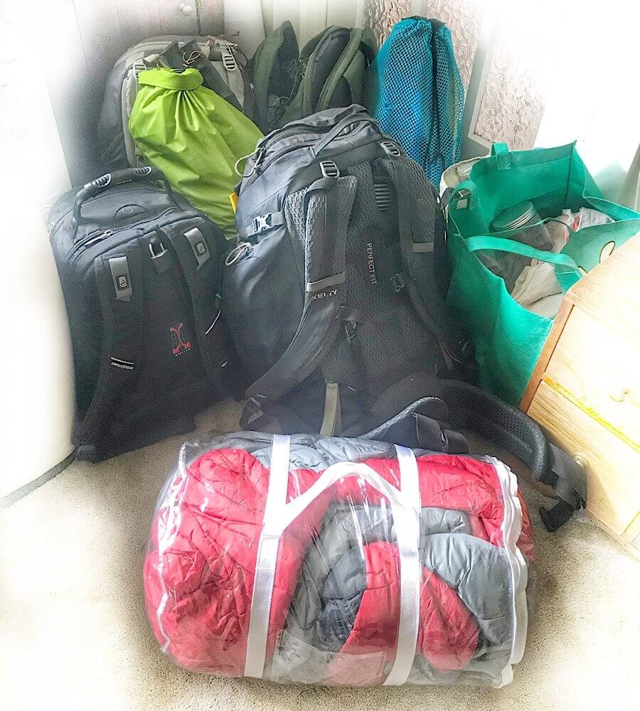 A sleeping bag, dry bag, tote bag, snorkel gear, and four backpacks in the corner at our house sit.