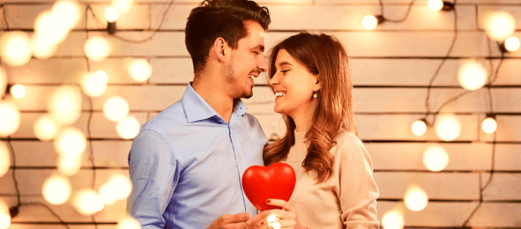 Couple holding a Red Heart and Looking Each Other