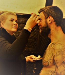Rachel Collins applies makeup to Jay Jay Ferguson