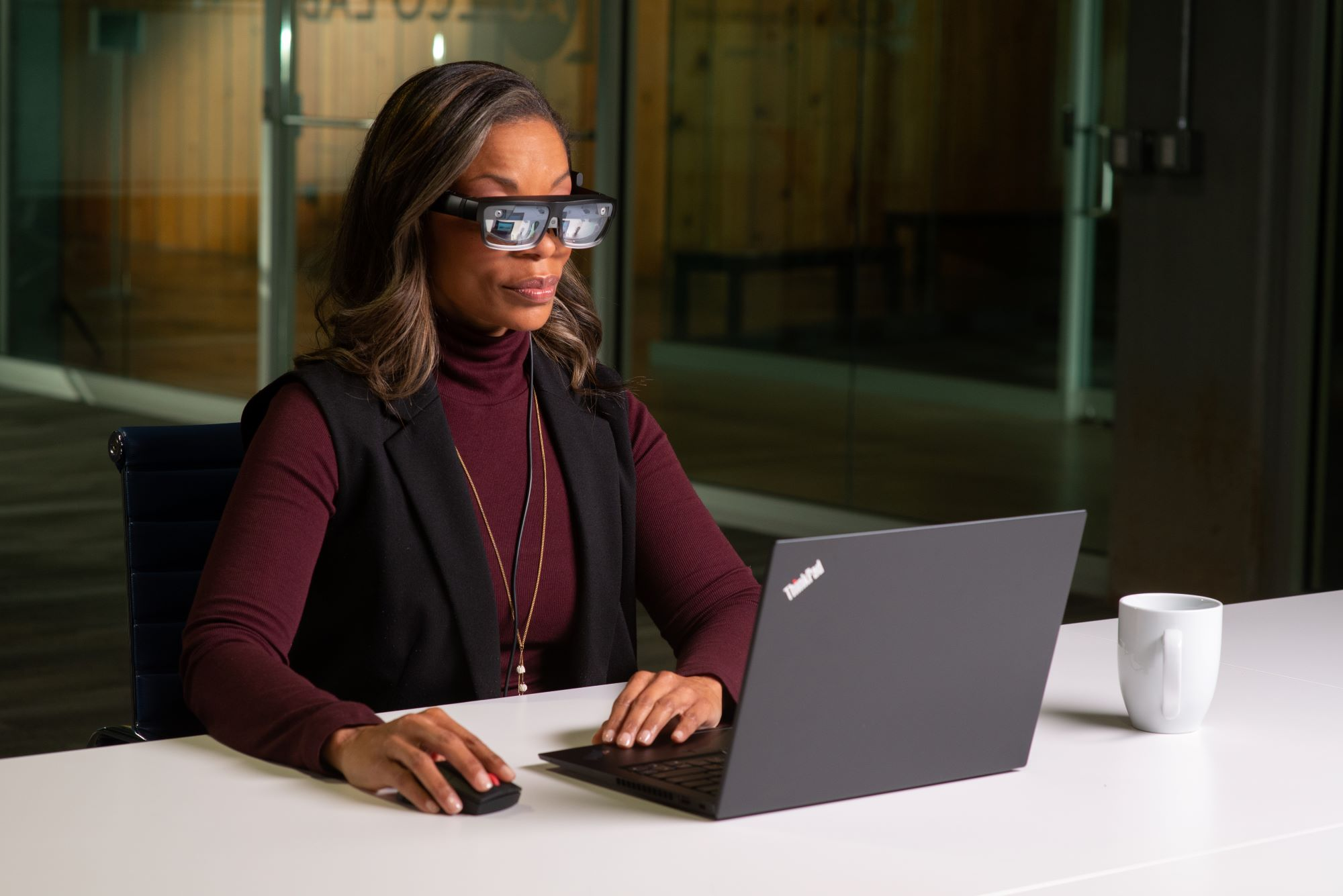 Woman wearing ThinkReality A3 glasses sitting in front of a Lenovo laptop
