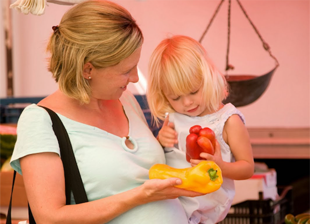 A woman caregiver with a toddler at the grocery store, both are holding peppers