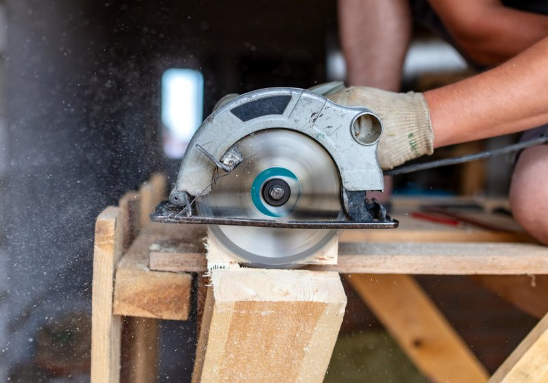 worker saws wooden beam building house   where can i learn basic carpentry skills