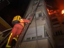 This handout picture taken and released by the Paris firefighters brigade in the night of February 5, 2019 shows a fireman climbing up a ladder as a fire burns in a building in Erlanger street in the 16th arrondissement in Paris