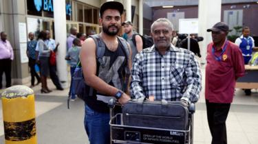 Passenger Ahmed Khalid who missed his Ethiopian Airlines Flight pictured with his father