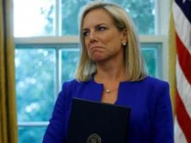 Former US Homeland Security Secretary Kirstjen Nielsen holding an executive order on immigration policy