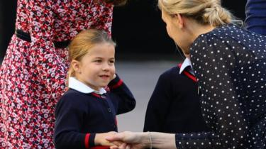 Princess Charlotte shakes hands with the head of the lower school