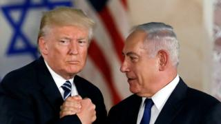 Donald Trump and Benjamin Netanyahu grasping hands in front of their national flags