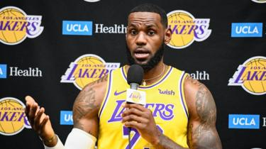 LaBron James stands with a microphone in hand as he talks to media