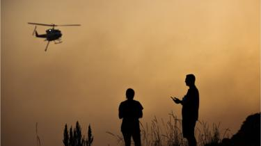 Silhouettes figures watch a helicopter against a sky turned orange from a bushfire at Forster, New South Wales on 7 November