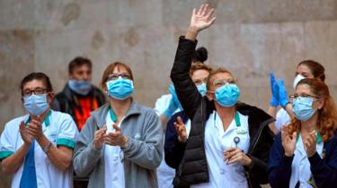 Medical workers react as they take part in the nationwide daily gratitude applause