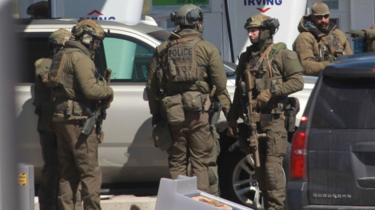 Members of the Royal Canadian Mounted Police (RCMP) tactical unit confer after encountering the suspect in a deadly shooting rampage