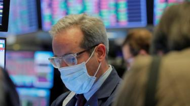 A trader wears a mask as he works on the floor of the New York Stock Exchange.