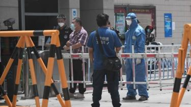 Security guards at a residential area under restrictions near Yuquan East Market in Beijing