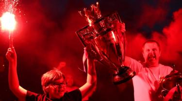 Two Liverpool fans celebrate with replica Premier League trophy outside Anfield