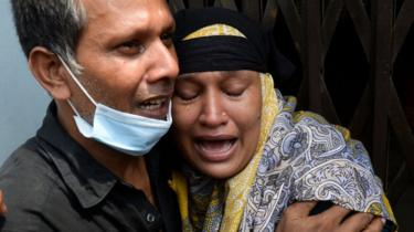Relatives of a victim of a ferry capsized mourn as rescue workers unload bodies in Dhaka on June 29, 2020