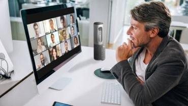 A man talks to 12 colleagues on Zoom's video conferencing app