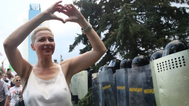 Maria Kolesnikova making a heart sign with her hands in front of a group of riot police in Minsk