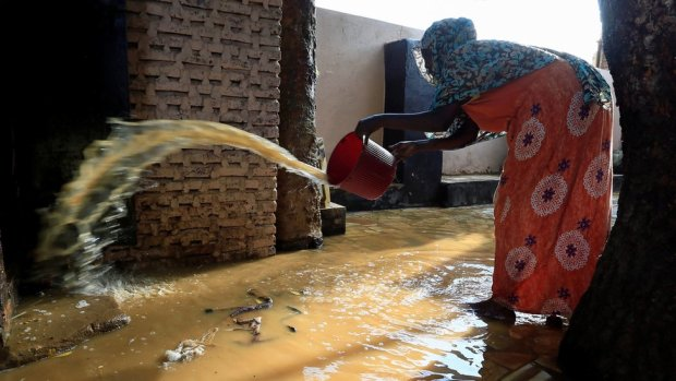 A resident pours out the waters of the Blue Nile floods from her backyard within the Al-Ikmayr area of Omdurman in Khartoum